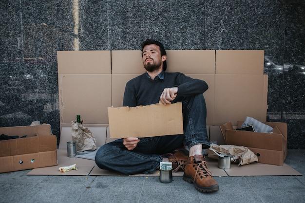 Безнадежный и бездомный человек сидит на картоне на земле и держит кусок картона