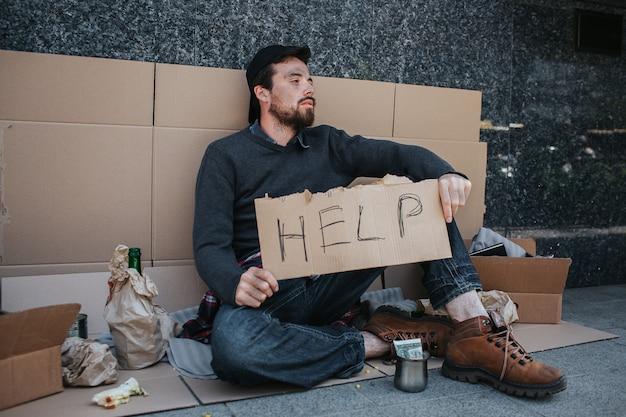 Грязный человек сидит на земле и держит в руках картон помощи. он смотрит в сторону. рядом с ним много вещей. также перед ним чашка с деньгами.