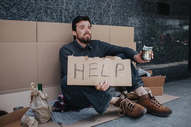 黒髪の男は段ボールの上に座って、助けを言う看板を持っています。