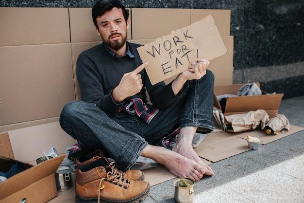 暗い髪とひげを生やしたホームレスの男性は座って、食べるための仕事を言う段ボールの部分を指しています。