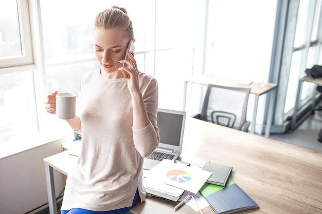 ビジネスの女性は彼女のオフィスのテーブルに立っていると電話で話しています。