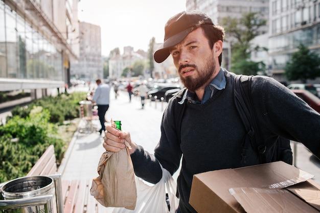 スタイリッシュなホームレスの男性が路上で外に立って、紙と箱で覆われたボトルを保持しています