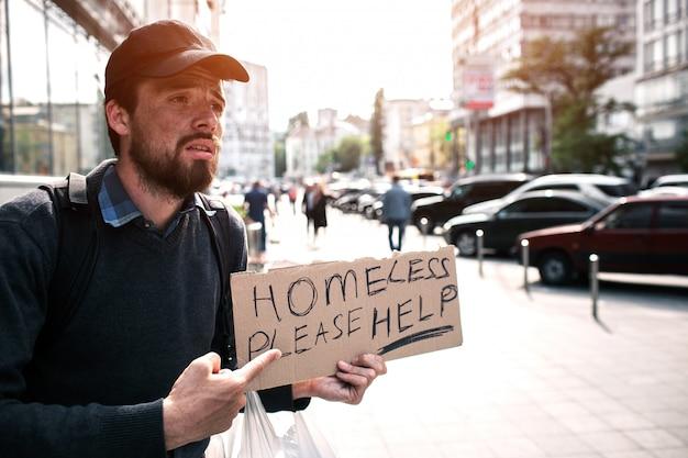 男は通りに立って、ホームレスを助けてくださいと言う段ボールの部分を指しています