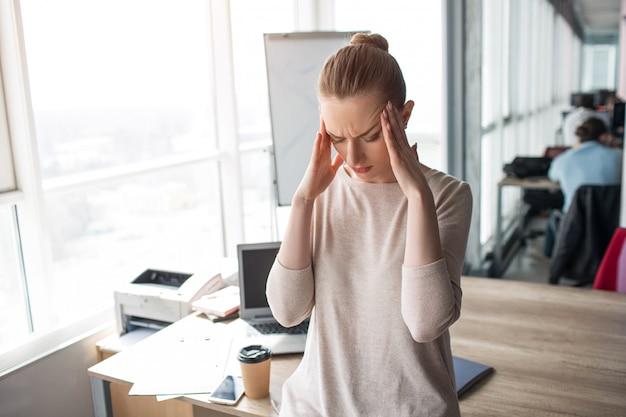 若い女性が大きな事務室に立って、彼女の手を頭の近くに保つ