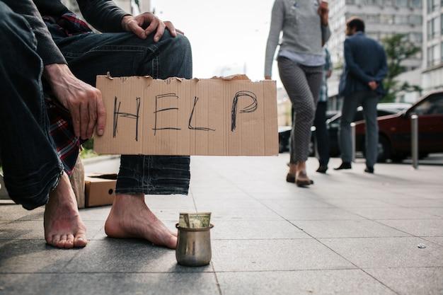 コンクリートの地面に立っている靴なしの男の足
