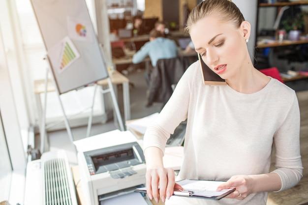 事務室に立って、電話に話している女性