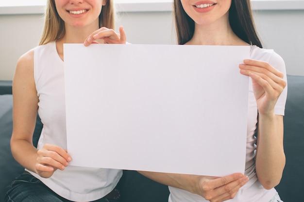 Женщины держат пустую белую бумагу