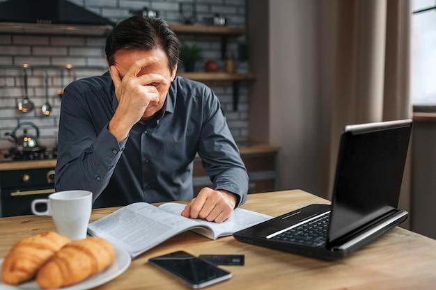 疲れた男は台所のテーブルに座っています。彼は手で顔を覆います。男の仕事。彼は頭痛がします。