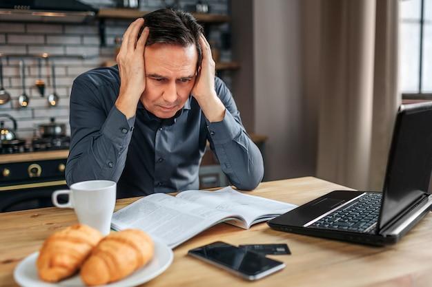 Серьезный концентрированный человек сидеть за столом на кухне. он держится за руки, слышит и читает журнал. человек работает.