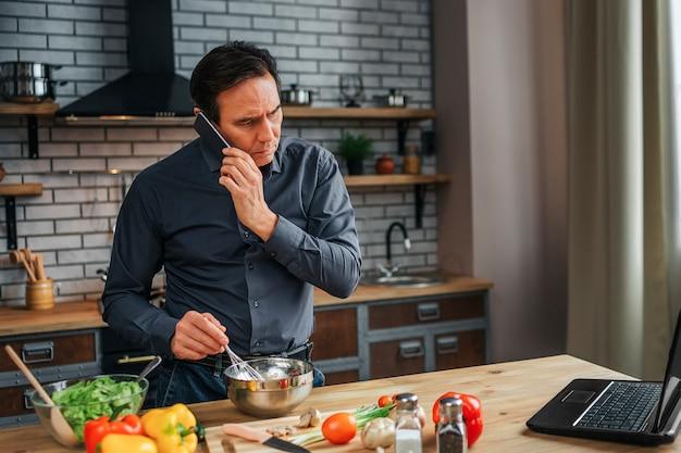 Серьезный концентрированный человек стоять на кухонном столе и смотреть на экран ноутбука. он разговаривает по телефону и смешивает яйца в миске. красочные овощи, лежа на столе.