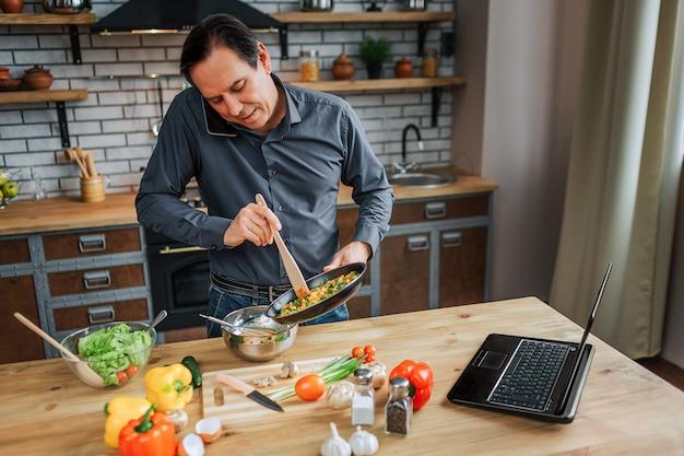 Занятой человек стоять за столом на кухне и смешивать яйца. он говорит по телефону и смотрит вниз. красочные овощи, лежа на столе.
