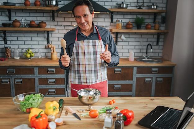 陽気な男は台所のテーブルに立って、カメラを見てください。彼は木のスプーンを持ち、大きな親指を立てます。ノートパソコンとテーブルにカラフルな野菜。