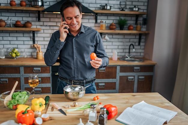 忙しい人は台所のテーブルに立ち、電話で話します。彼は笑顔で卵を手に持っています。男の料理。テーブルの上のカラフルな野菜。