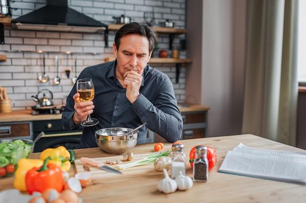深刻な男は台所のテーブルに傾いて、見下ろしています。彼は白ワインのグラスを持ち、あごに手をつけます。カラフルな野菜とテーブルの上のジャーナルとスパイス。