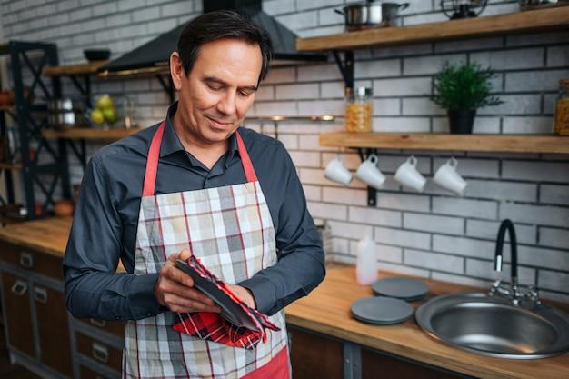 慎重に大人の男が台所で皿を乾燥させます。彼は皿を見て、少し微笑んでいます。部屋で一人で。エプロンを着用してください。