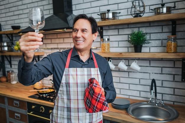 エプロンの素敵な大人の男が一人で立ち、キッチンでガラスを見てください。きれいに輝きます。男はキッチンタオルと笑顔を保持します。