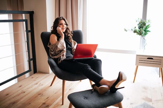 若い実業家が自宅で仕事します。椅子に座って、小さなスツールに足を保持している忙しいモデル。電話で話しています。忙しい女性は膝の上にラップトップを保持します。リモートワーク。リビングルームで一人で。