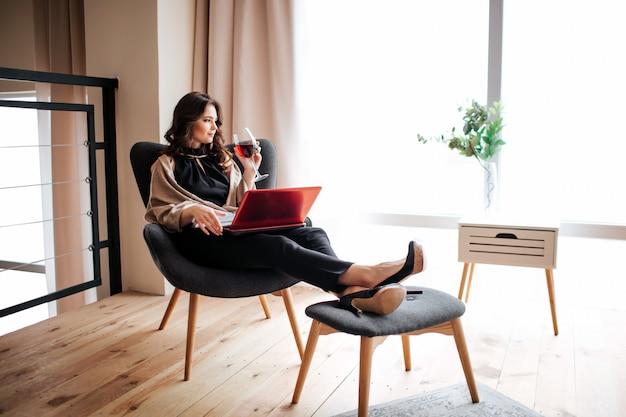 若い実業家が自宅で仕事します。椅子に座って、グラスから赤ワインを飲みます。リモートワーク。膝の上の赤いラップトップ。リビングルームで一人で。明け。
