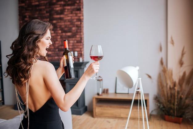 若い女性はアルコールに問題があります。黒のスーツの美しいしっかりとしたスリムなモデルは、ワインとボトルとグラスを保持します。立ち上がって叫びます。リビングルームで一人で。