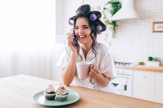 電話で話している美しい女性主婦を引き付けます。カップを手に持って。プレート上のパンケーキ。ゴシップ。カーラーで髪をブルネット。仕事のないのんきな生活。ホームアローン。