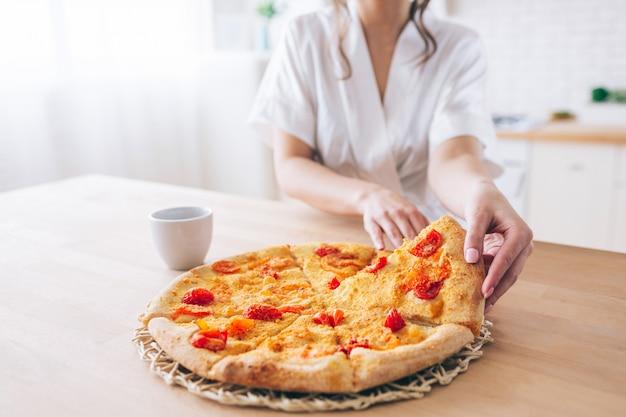 キッチンで白いドレッシングガウンの女性のビューをカットします。ピザを取ります。小さなスライス。若い家政婦はのんきな生活をしています。