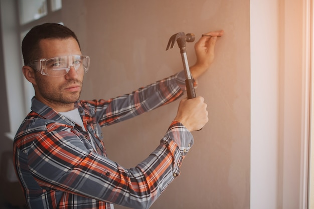 Строитель работает на стройке. работник с ведром и краской валик возле стены.