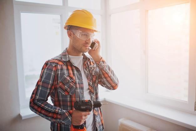 Рабочий или строитель держит электродрель и разговаривает по телефону. концепция строительства или ремонта. на фоне строительства