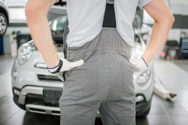 男性の体の写真は車の前に立っています。男は腰に手を保持しています。彼は手袋を着用しています。カメラに見せられた彼のお尻です。