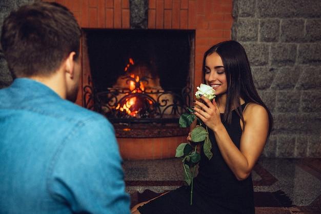 素敵な若い女性は白いバラの香りがします。彼女はそれを顔の近くに保持して見て、ガイはカメラに戻って座っています。彼らは暖炉の近くにあります。