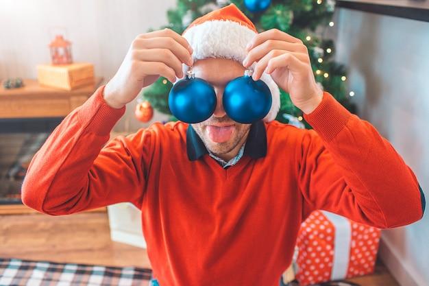 面白い若い男は、手で目におもちゃを保持しています。彼らは青です。彼はそれで遊ぶ。