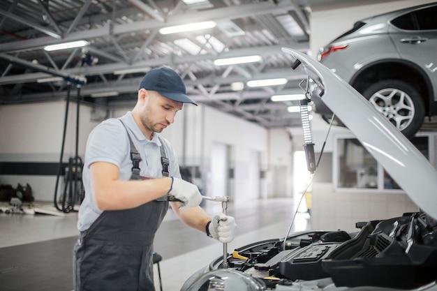 若年労働者は車の開いた体に立っています。彼は大破を使用して修正します。彼は真剣で集中しています。男はガレージで働いています。