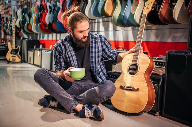 Молодой хипстер отдыхает, сидя на полу. он держит чашку в руке. еще один касается акустической гитары рядом с ним. молодой человек смотрит на инструмент.