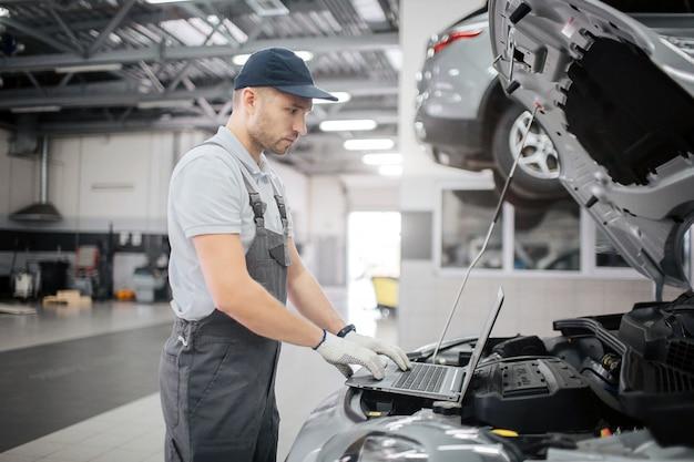 キーボード上の若年労働者のタイプの写真。彼はラップトップの画面を見ます。ガイは車の診断を行っています。彼はその状態をチェックします。