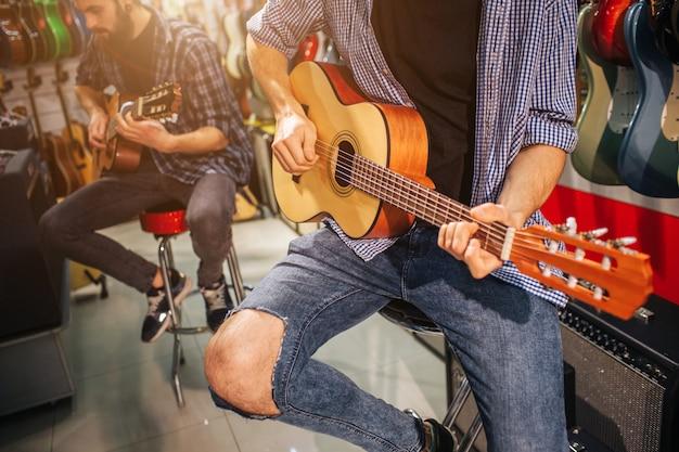 Два музыканта играют на маленьких акустических гитарах. они сидят на специальном стуле. многие электрогитары позади них.