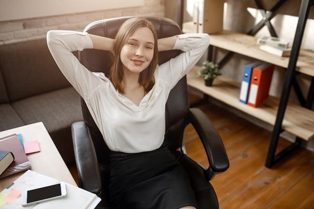 仕事中に休憩を持つ若い女性。彼女は頭の後ろで手をつないで微笑んでいます。彼女は部屋に座っています。