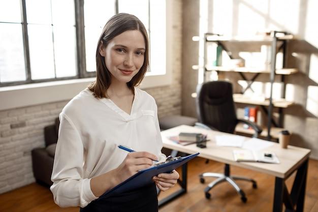 Веселый молодой предприниматель стоять в комнате и смотреть на камеру. она держит пластиковую папку с документом и пишет.