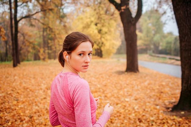 若い女性は秋の公園に立って、カメラを振り返ります。彼女は真剣です。若い女性は耳にヘッドフォンを持っています。彼女は音楽を聴いています。