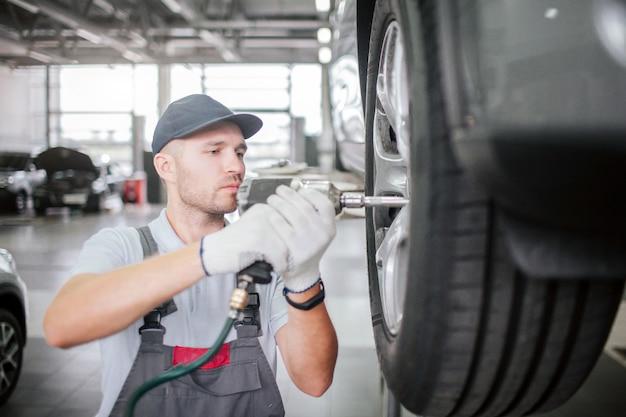 制服を着た若い男は、修理用ホイールのプラットフォーム上にある車に立ちます。彼はそのために特別なレンチを使用しています。労働者は真面目で集中しています。