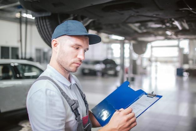 ガレージに立っている労働者の写真。彼は真面目です。ガイは紙でプラスチックのフォルダーを持ち、ため息をついています。男は灰色の制服と帽子を着ています。