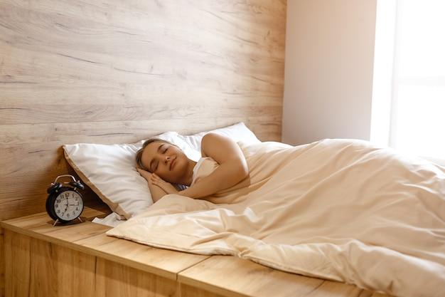 Молодая красивая белокурая женщина лежа в кровати в утре. она спит мирно и спокойно. маленькая улыбка на ее лице. черный будильник стоит возле стола. дневной свет. утренний сон.