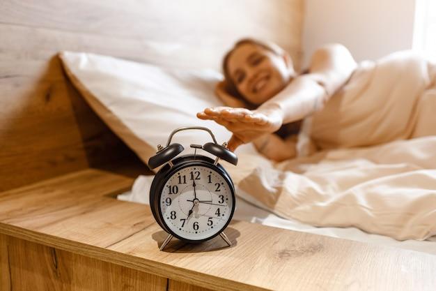 Молодая красивая белокурая женщина лежа в кровати в утре. положительная счастливая модель достигая будильник с рукой. , дневной свет. хорошее настроение.