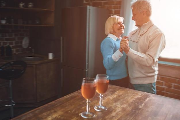 台所で一緒に踊る老夫婦の素敵で暖かい写真。
