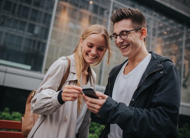 Пара или друзья смеялись и веселились с помощью смартфона на улице большого города.