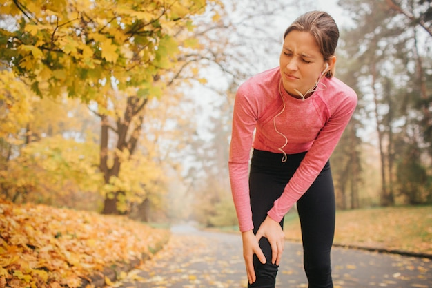Стройная и стройная молодая женщина стоит на дороге в осенний парк. она держит руки на колене. модель чувствует там боль. она страдает.