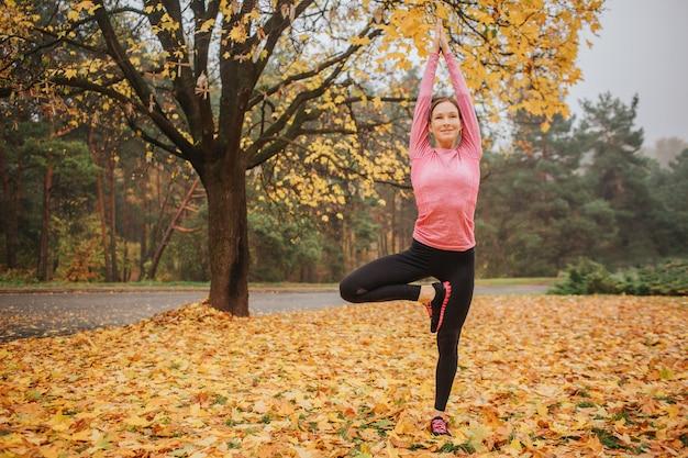 穏やかで、平和的で前向きな若い女性がアーサナの位置に立ち、まっすぐに見えます。彼女は手を上げます。女性は一人で秋の公園にいます。