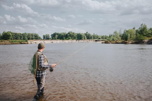 Изображение человека стоящего в воде и рыболовстве. он держит в руках спиннинг и смотрит на воду. парень имеет рыболовную сеть на спине. он выглядит спокойным и сосредоточенным.