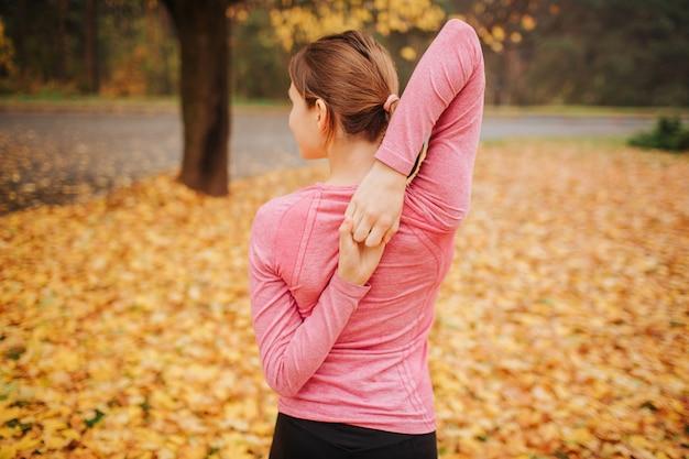 Изображение молодой женщины стоит в парке осени и смотрит налево. она протягивает руки. женщина держит их вместе за спиной.