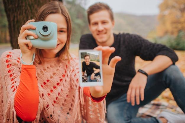 若い男性と女性の写真は真っ直ぐに見え、笑顔です。彼女は青いカメラと写真を手に持っています。写真に黒い服を着た若い男がいます。