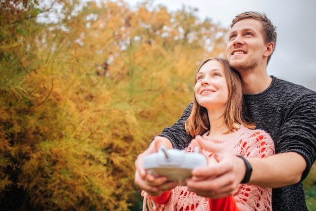 幸せで陽気な若い男と女が見上げます。彼らは一緒にリモートコントロールを保持します。秋の公園に立っている人。