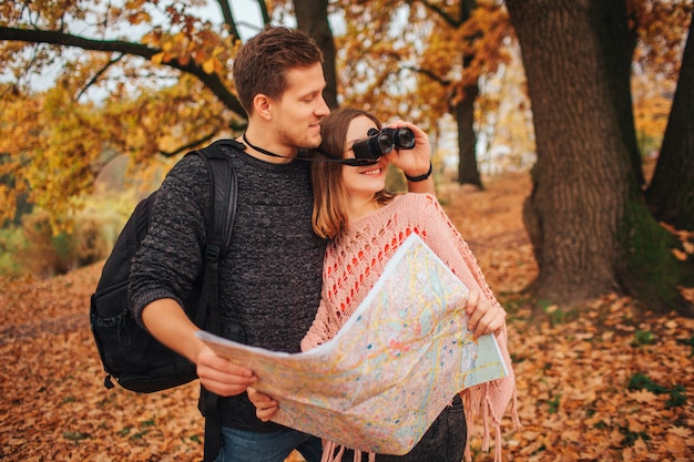 ハンサムな男性は女性のほかに立ち、双眼鏡を持ちます。彼女はそれを見ます。彼らは一緒に地図を保持します。人々は公園にいます。